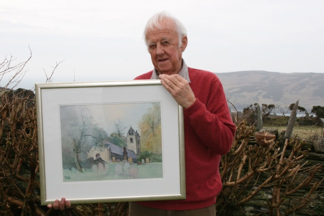 Manx artist David Byrne with his watercolour of Old Kirk Braddan Church which will be a raffle prize at the Isle of Man Art Society's Easter Art Exhibition sponsored by Manx Telecom.